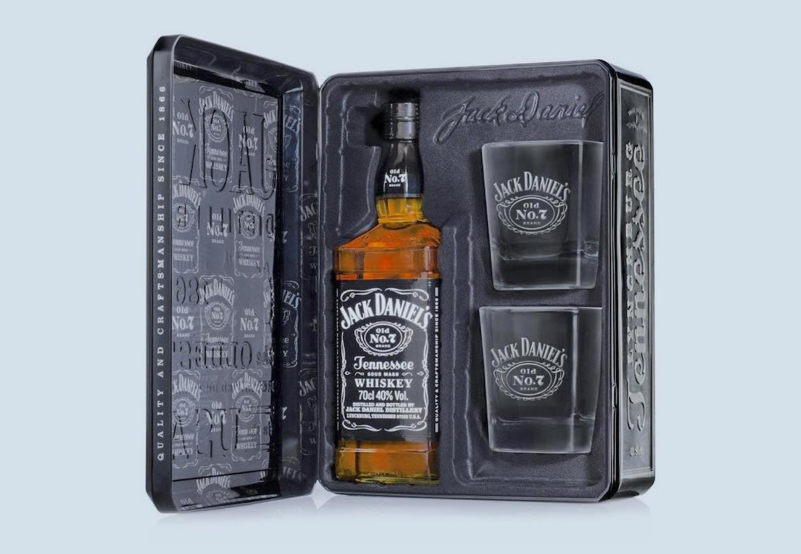A whiskey bottle and two cups in a black tin gift box